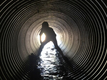 Rear View Of Silhouette Boy Standing In Sewage Tunnel
