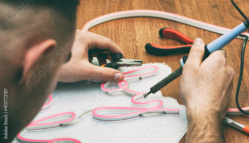 Obraz The worker is production the sign made from the led neon ribbon - fototapety do salonu