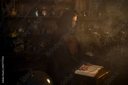 Fotografie, Tablou Male exorcist in black hood reads a spell