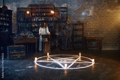 Photo Young demonic woman reads book of spells