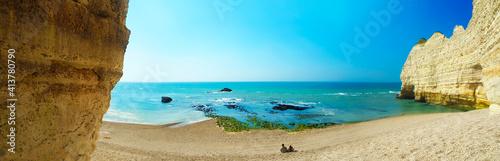 Fotografie, Obraz Picturesque panoramic landscape, La Porte d'Amont natural rock arch wonder, tourists, waves on pebble beach