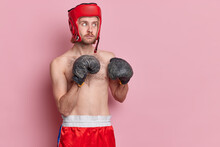 Serious Man Poses In Boxing Gloves Ready To Punch Prepares For Competition In Gym Wears Protective Hat And Shorts Isolated Over Pink Background With Copy Space For Your Promotion. Sport Concept