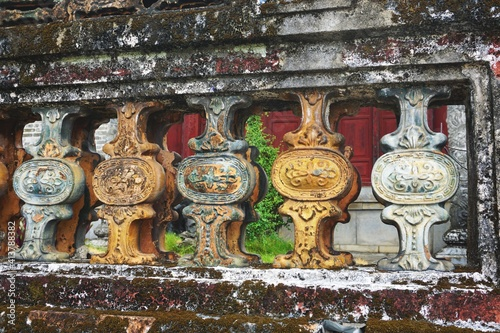 Cuadros en Lienzo Glazed ceramic ornamental balusters set in ancient moss-covered fence in Southea