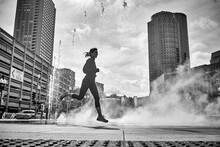 A Woman Running Past A Fountain In The Greenway Of Boston.