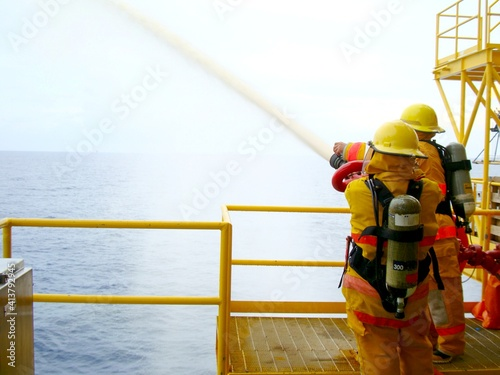 Fire drill training on board for the crew in ship on offshore plant form oil and gas with fireman, fire hose, water spray, and blue sky, sea background Fotobehang