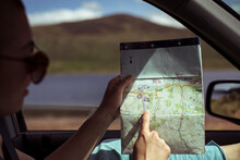 Person On Road Trip In Car Points At Old Map