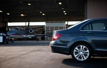 Car Parked At Airplane Hangar
