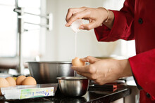 Cropped Image Of Woman Breaking Egg In Bowl