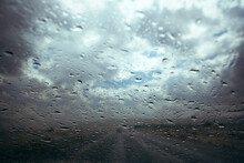 Road Against Cloudy Sky Seen Through Wet Windshield