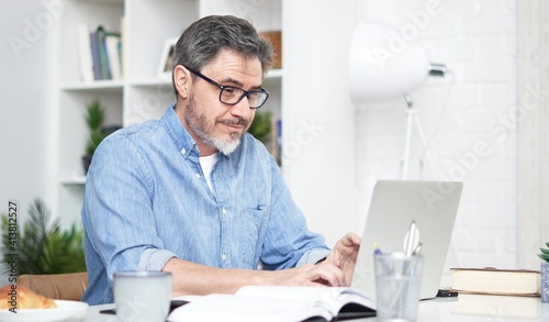 Fototapeta Older man working online with laptop computer at home sitting at desk. Home office, browsing internet, study room. Portrait of mature age, middle age, mid adult man in 50s. obraz