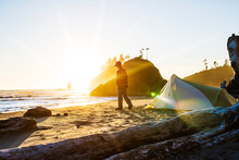 Teenager Walking By Tent On Sea Shore Against Clear Sky