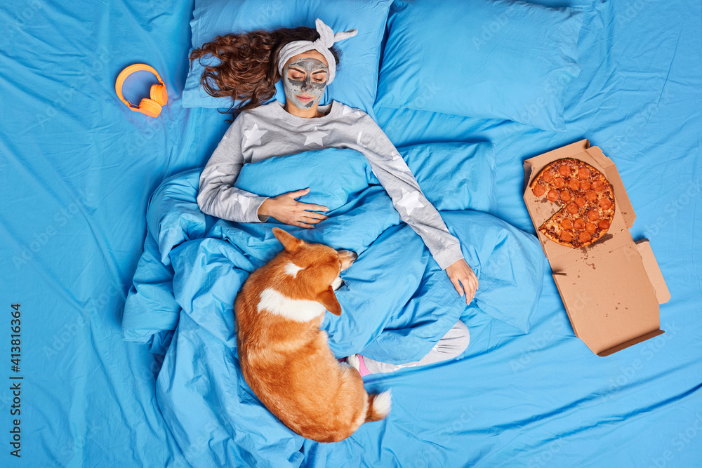 Fototapeta Pleased brunette young woman applies clay mask on face undergoes beauty mask before sleeping looks at her dog pose on comfortable bed under soft blanket awake in cozy bedroom. Wake up in morning