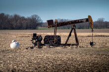 An Old Rusty Oil Pump Jack With Support Equipment Sits In Harvested Cornfield In American Midwest Where Farmers May Have Pumps On Their Property.