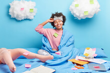 Happy Beautiful Young Woman Stretches In Bed Enjoys Good Morning Wrapped In Soft Blanket Surrounded With Papers Prepares For Examination Session Being At Home On Self Isolation And Quarantine