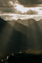 Golden Light Bursts Through Clouds Into Beautiful Mountain Valley