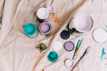 Cans Of Colorful Paint From A High Up Angle On A Drop Cloth.