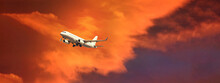 Ultra Wide Panoramic Zoom Photo Of Passenger Airplane Taking Off At Sunset With Beautiful Orange Sky And Clouds