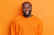 Leinwandbild Motiv Portrait of cheerful bearded African American man has happy expression smiles broadly has white perfect teeth wears hat and sweater isolated over orange background. Positive emotions concept