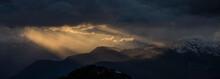 Sun Beams Shining Through Clouds Over A Panorama Mountain Landscape.