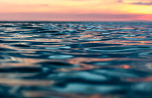 Sunset Over Glassy Ocean And Calm Waters