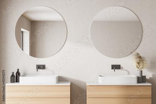 Fototapeta Modern bathroom with white walls, two sink with round mirrors and left window light. obraz na płótnie