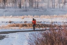 Photographer Walking On Bike Path Next To Frozen River In Calgary