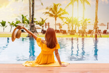 Young Woman Traveler Relaxing And Enjoying The Sunset By A Tropical Resort Pool While Traveling For Summer Vacation