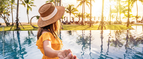 Fotografie, Obraz Young couple traveler relaxing and enjoying the sunset by a tropical resort pool