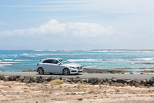 Grey Car Driving Empty Paved Road With Ocean In The Background