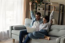 Shocked Young Family Couple Cuddle On Sofa Raise Hands Scream Wow Read Email With Great News On Laptop Screen. Lucky Husband Wife Celebrate Winning Lottery Getting Great Offer Proposal For Purchase