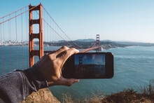 Tourist Taking A Photo Of The Golden Gate Bridge In San Francisco