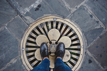 Someone Standing On A Fancy Metal Manhole Cover Black Shoes And Jeans