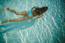 A Young Girl Wearing An Aqua Swimsuit Swims Underwater