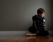 Preteen Boy Sitting On Floor With Video Game Controller In Hand.