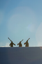 Three Skiers Walking At Sunrise In British Columbia Canada