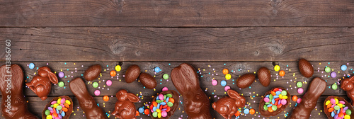 Obraz Easter candy and chocolate bunnies and eggs. Bottom border against a rustic dark wood banner background. Copy space. - fototapety do salonu