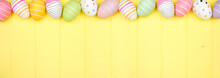 Colorful Easter Egg Top Border Over A Soft Yellow Wood Banner Background. Overhead View With Copy Space.
