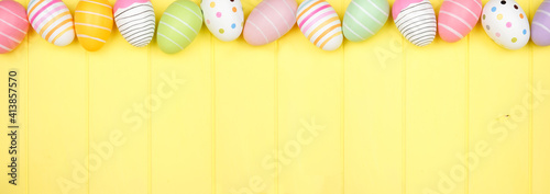Fototapeta Colorful Easter Egg top border over a soft yellow wood banner background. Overhead view with copy space. obraz