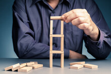 Man Build A Ladder Tower By Wooden Domino And Risk To Make It All Down, Business Plan And Risk Management Concept