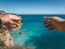 POV View Of Ocean Between Outstretched Hands