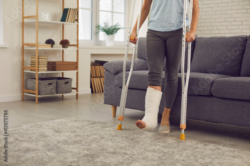 Valokuva Woman with broken injured leg in cast standing with metal crutches during rehabilitation at home with room interior at background