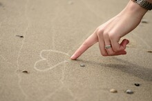 Hand Drawing Heart In Sand