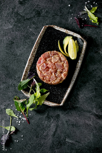 Fototapeta Tuna tartare with green salad, lime, avocado and mustard sauce serving on japanese style black ceramic plate over black marble background. Flat lay, copy space. Restaurant appetizer obraz