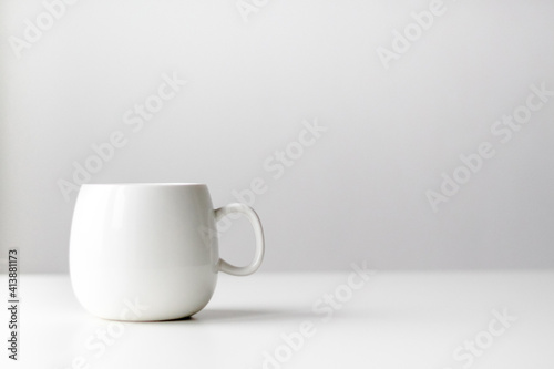 white cup and saucer on wooden table Fototapet