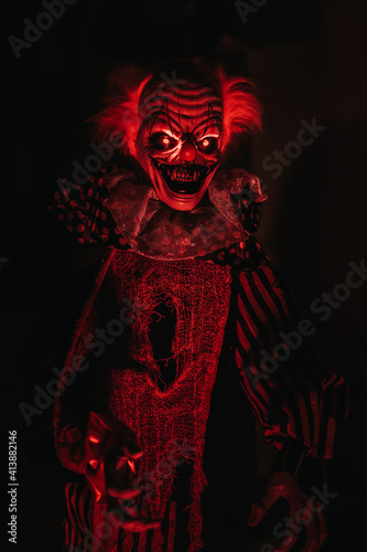 Cuadros en Lienzo Closeup view of a scary clown mannequin placed in the dark room with red lights