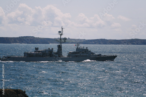 Fotomural French warship plies the ocean with coast in the background