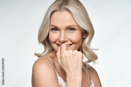 Fototapeta Happy smiling attractive 50s middle aged blonde woman looking at camera advertising antiage face skin and aging hair care treatment and cosmetics isolated on white background