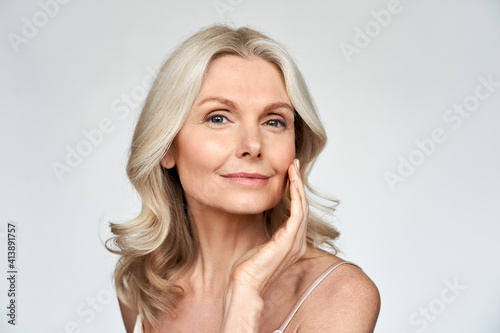 Obraz Beautiful gorgeous 50s mid aged mature woman looking at camera isolated on white. Mature old lady close up portrait. Healthy face skin care beauty, middle age skincare cosmetics, cosmetology concept - fototapety do salonu