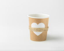 Empty Paper Cup Decorated With White Heart And Jute Thread On White Background