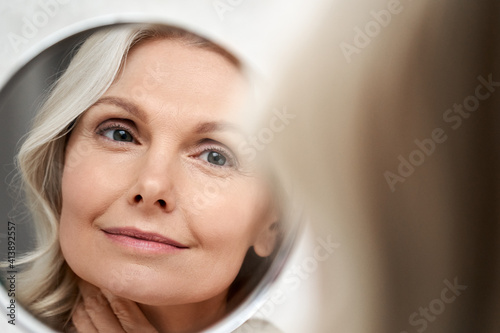 Fototapeta Happy 50s middle aged woman model touching face skin looking in mirror reflection. Smiling mature old lady pampering, healthy moisturized skin care, aging beauty, skincare treatment cosmetics concept. obraz